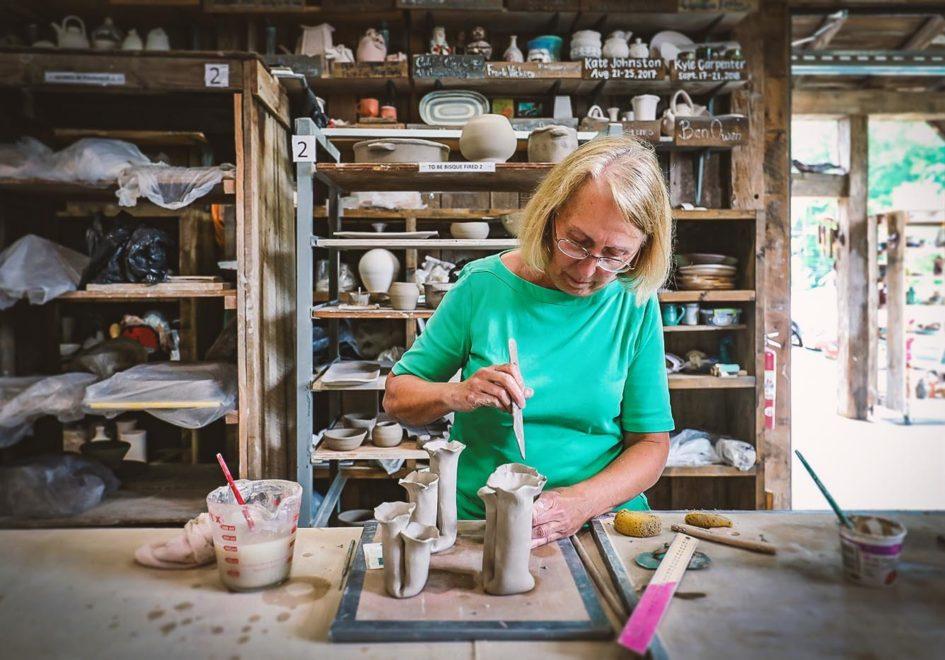 Artist Janet Chmar works on her bud vases at the Dave Drake Studio Barn.